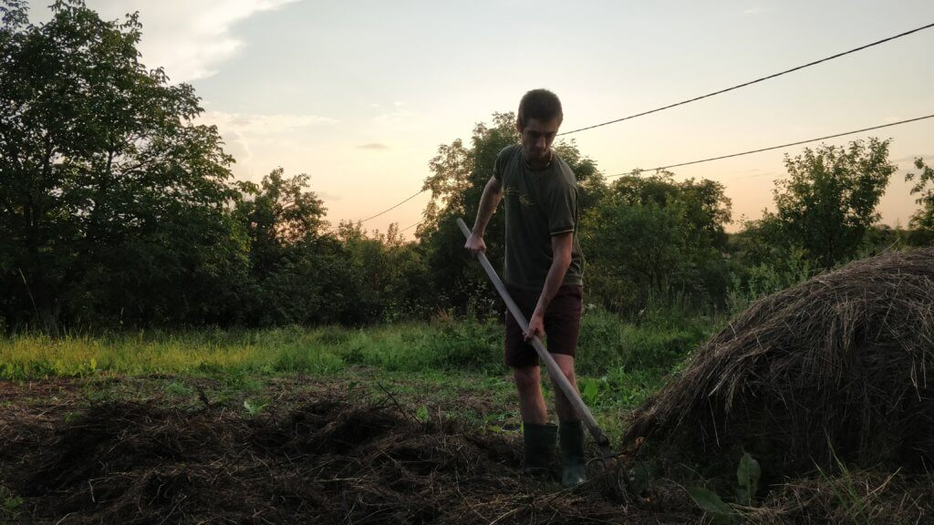 young man gardening with a pitchfork