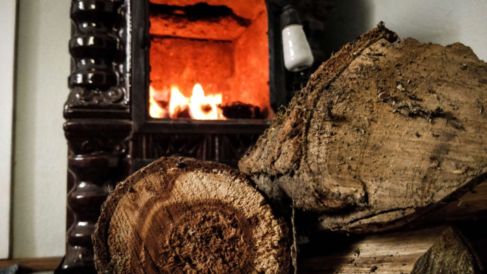 woodlogs by terracota stove with fire burning