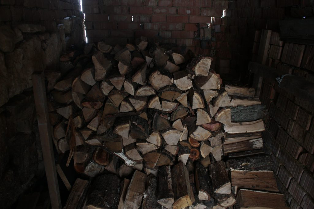 pile of cut and split firewood in woodshed
